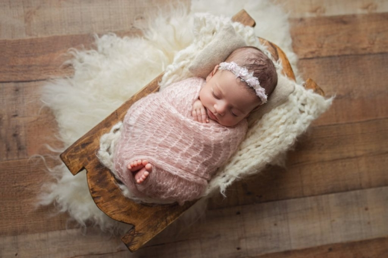Photo of first twin wrapped with toes peeking out and sleeping in a wooden prop during a newborn twin photo session