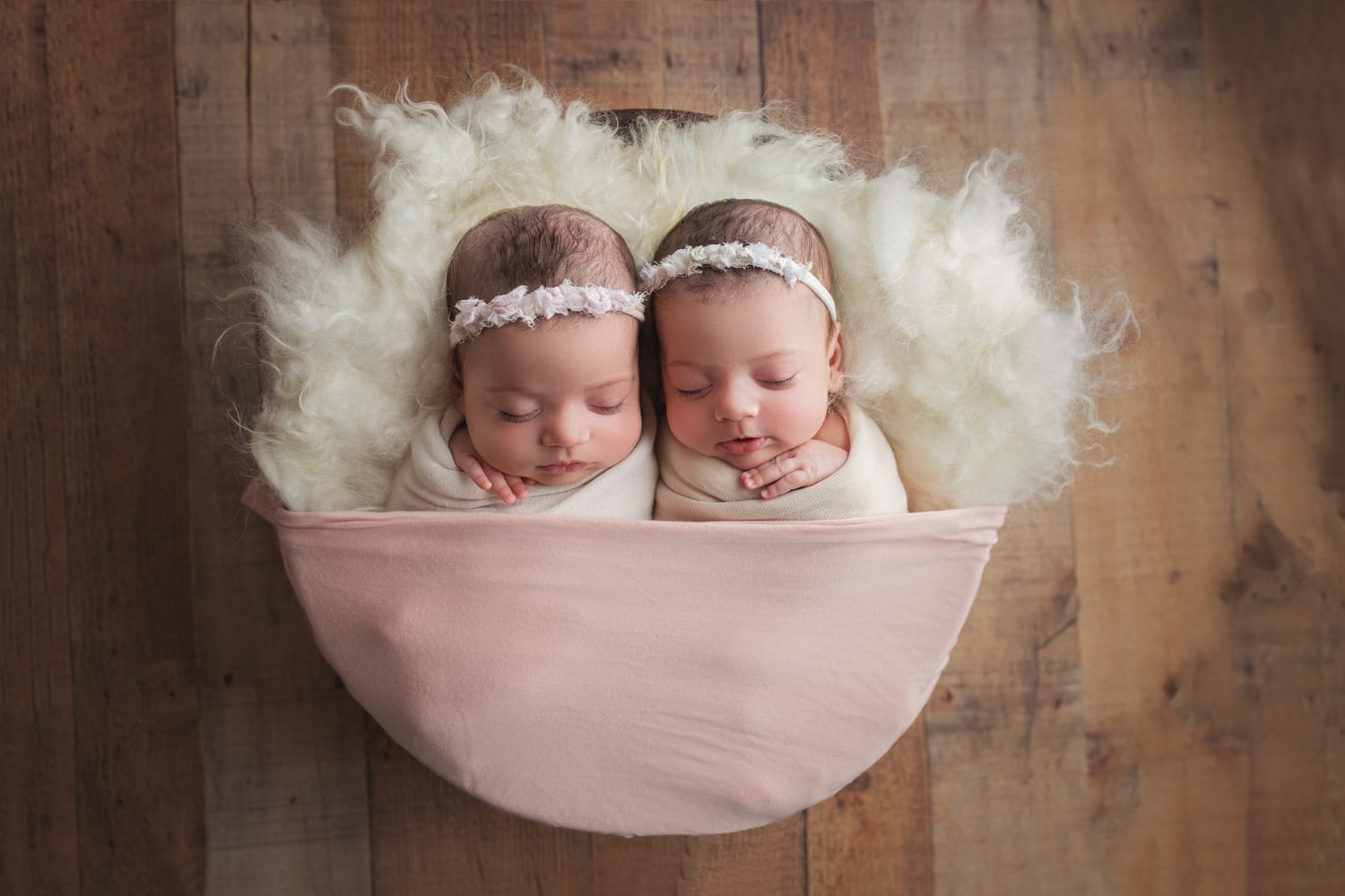 Two beautiful baby girls wrapped up during a twin newborn photo session at Yvonne Leon Photography studio
