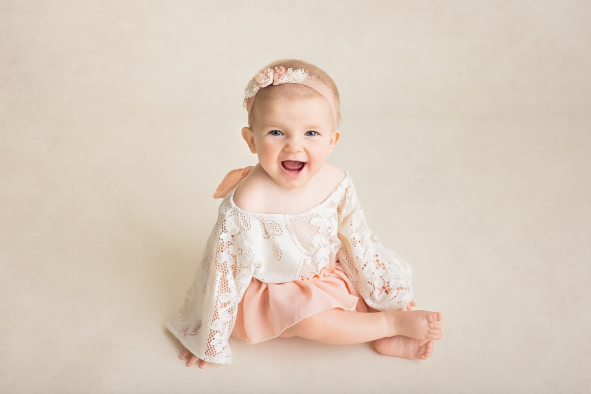 Baby girl in cute pink lace dress smiling at the camera during a sitter session at Yvonne Leon Photography