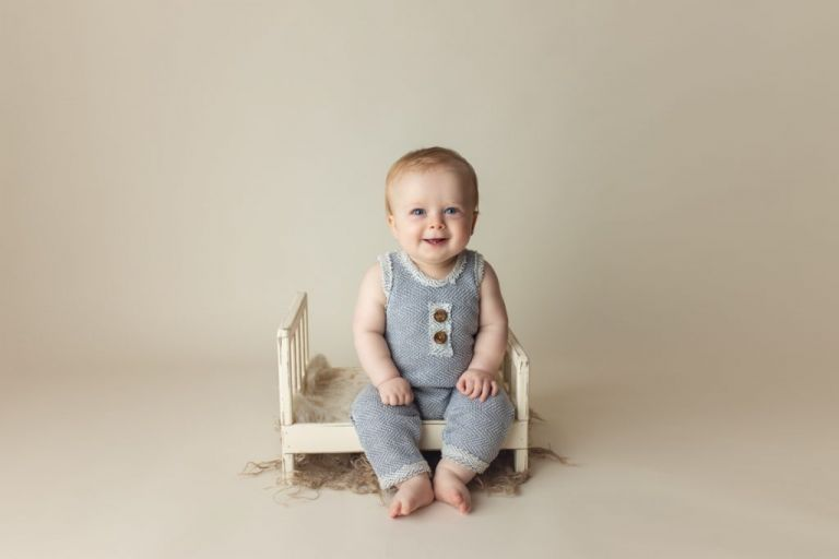 cute baby boy sitting in a photography prop that resembles a little bed.  Studio baby photography.