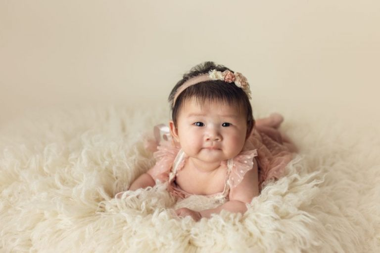 100 days old baby doing tummy time on a soft rug in a studio portrait at Yvonne Leon Photography