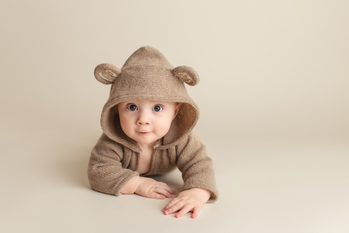 baby boy wearing cute teddy bear hoodie during a tummy time photo session