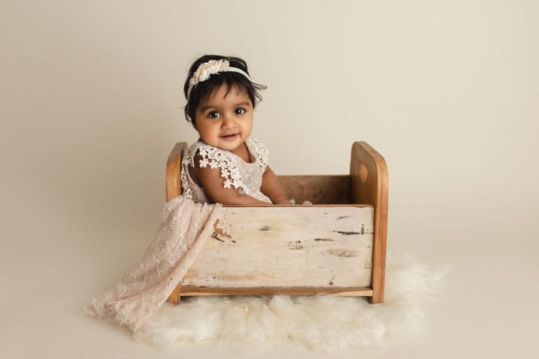 baby girl sitting in a little wooden bed photography prop for a sitter session baby photography.