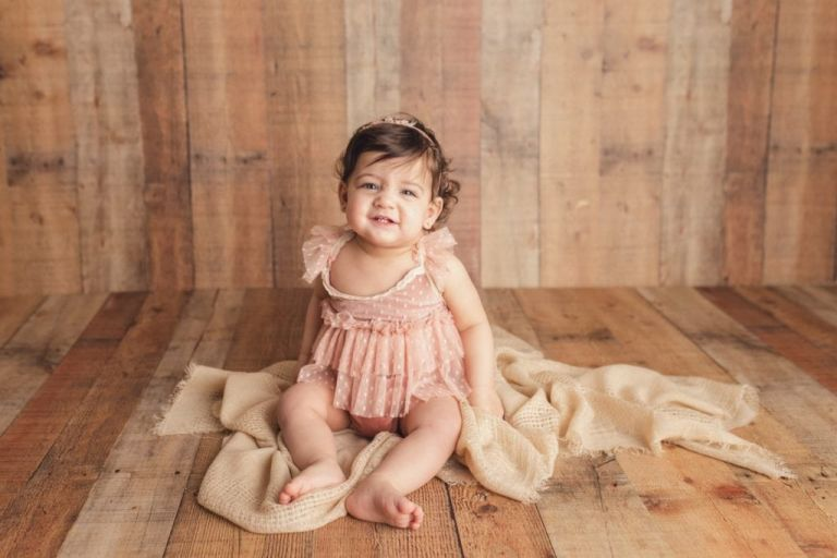 baby girl smiling at the camera and sitting up on a soft blanket.  Studio portrait.