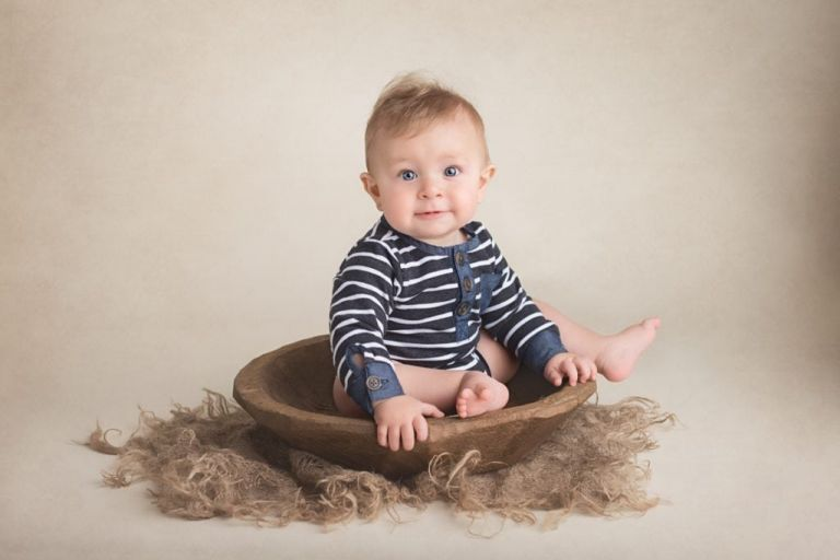 Baby boy sitting up in a large shallow wooden bowl.  Prop for baby photography.