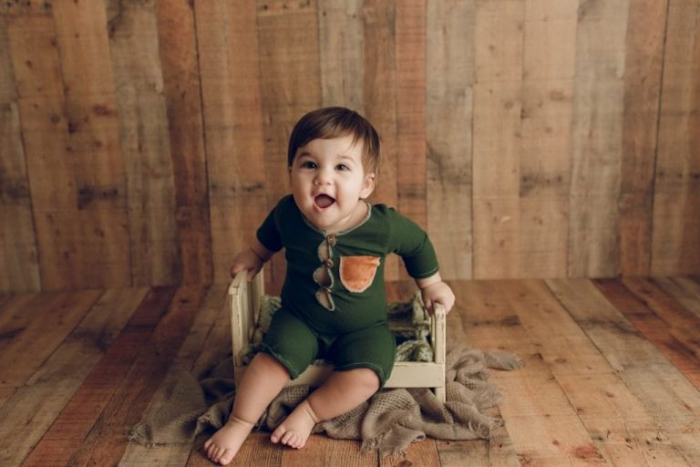 baby boy wearing a custom-made green jumper outfit sitting in a photography prop and smiling at the camera during a sitter session portrait.