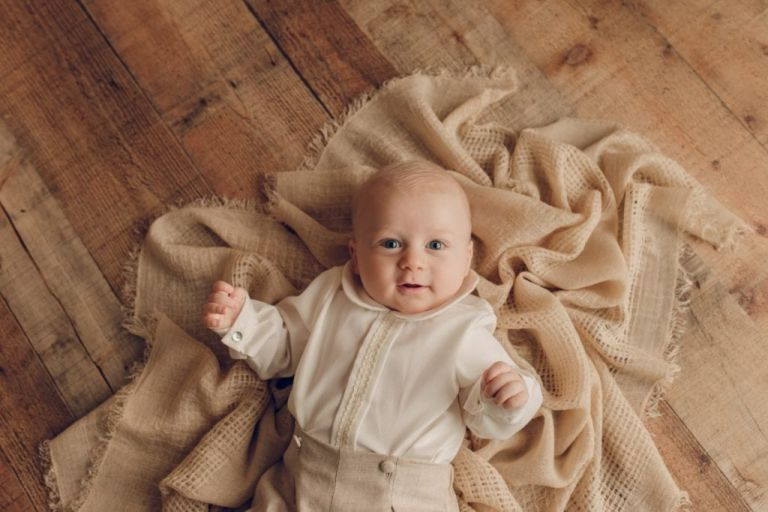 Baby boy wearing cute baby clothes laying on top of a blanket and looking up at the camera.