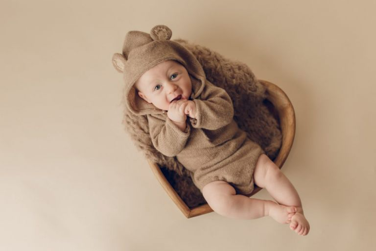 three month old baby dressed in a teddy bear outfit and laying in a prop looking up at the camera and smiling.