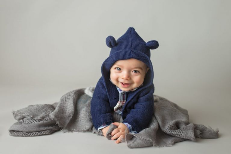 smiling baby boy in a blue teddy bear hoodie doing tummy time in a studio portrait.