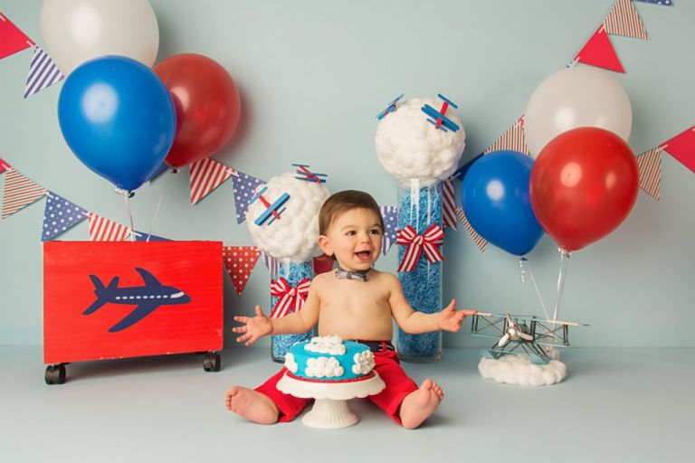 airplane themed cake smash setup with red, white and blue balloons, banners, and photography props.