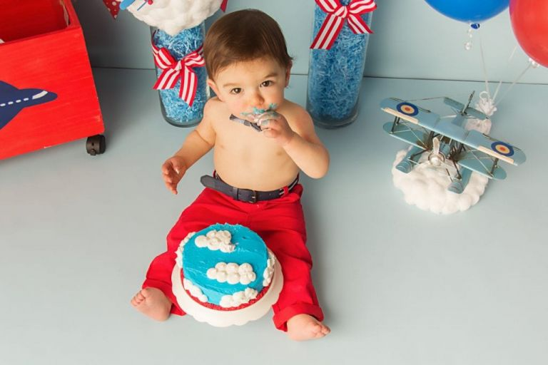 baby boy sitting in front of a birthday cake that is blue with white cloud frosting.  He is taking a taste of his cake during his cake smash photoshoot for first birthday.