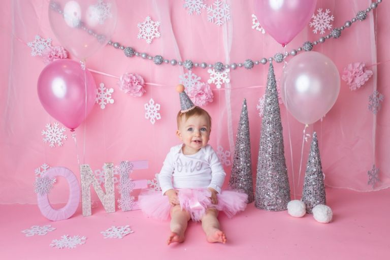 """baby girl wearing white onesie with word """"one"""" on front, pink tutu skirt and sparkly silver hat.  Waiting for her cake during a winter onederland cake smash photoshoot."""