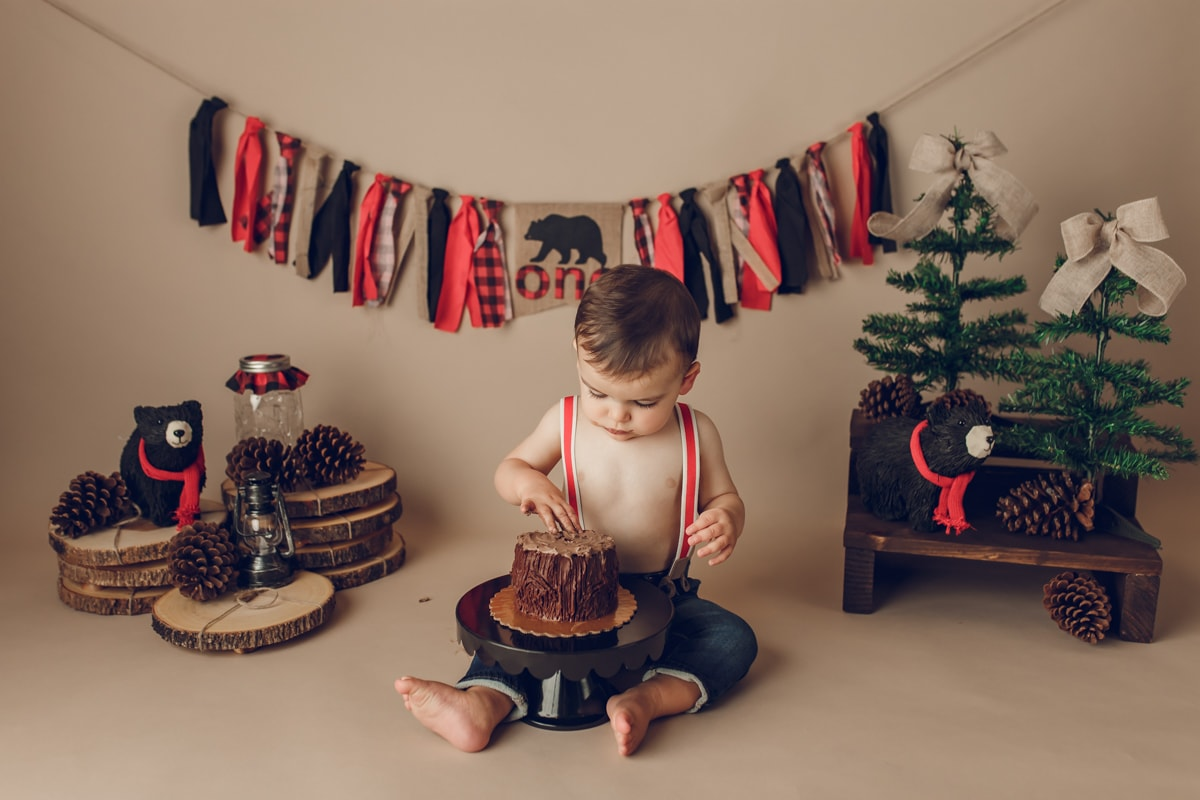 rustic winter cake smash with red and black buffalo plaid props by NJ Photographer Yvonne Leon