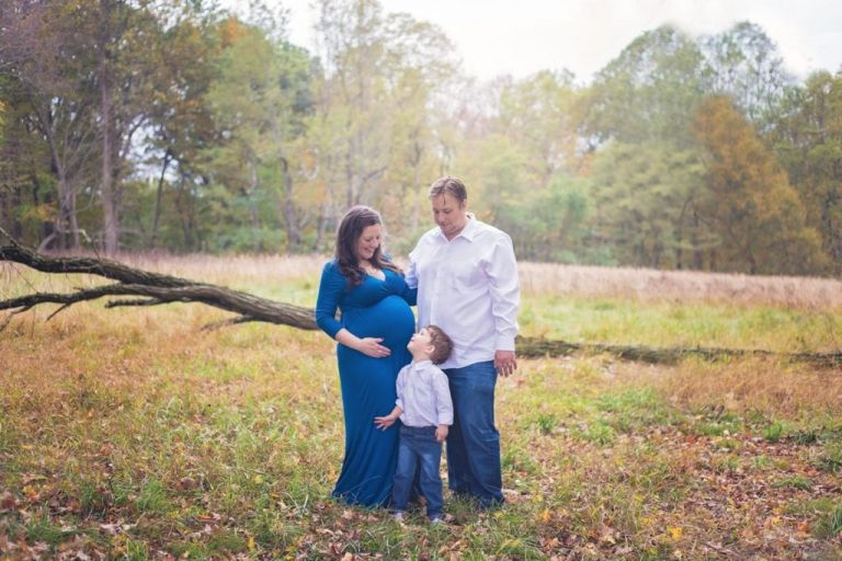 Family of three with mom, dad, and little boy all smiling at each other during an outdoor maternity photo shoot.  Little boy looks up at mom's belly.