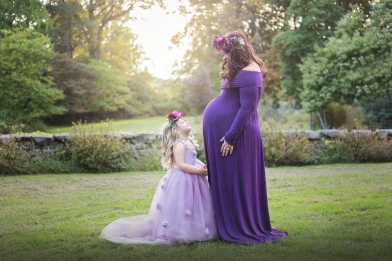 Mom and daughter smiling at each other during a maternity portrait session outdoors during the spring.