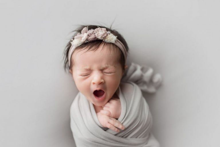 yawning newborn baby girl wrapped in grey and wearing a matching grey headband with bows and flowers.