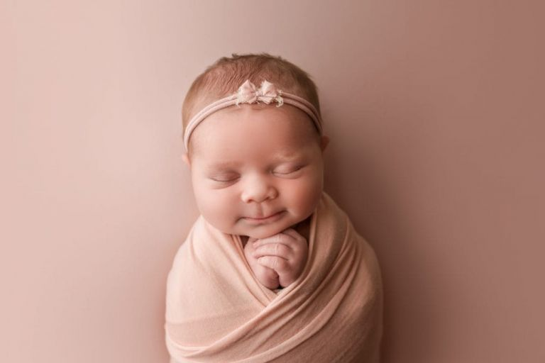 baby girl wearing a pink headband with little pink bow; newborn headband.