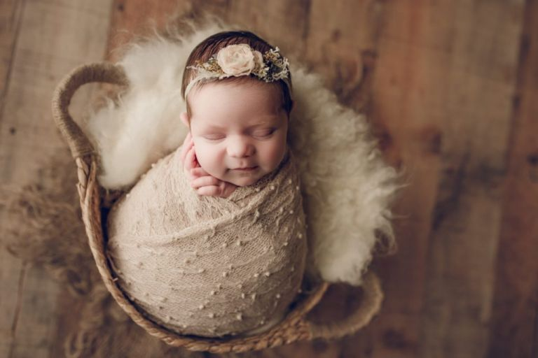 baby wrapped in potato sack and nestled into a basket prop.