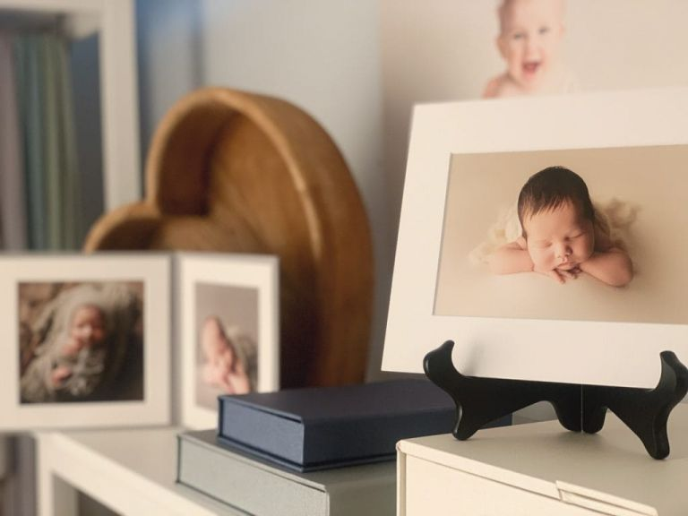 A bookshelf styled with product samples of newborn and baby portraits and albums.