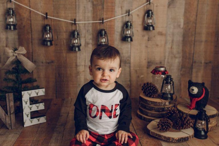closeup of baby boy with string of lanterns set up behind him.