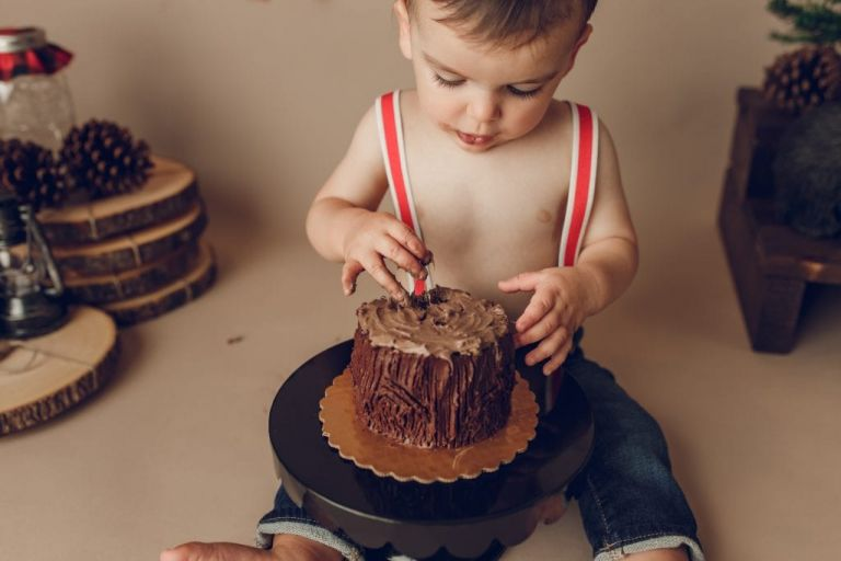 closeup of baby boy wearing red suspenders and about to put his fingers into a chocolate cake for a cake smash photoshoot.