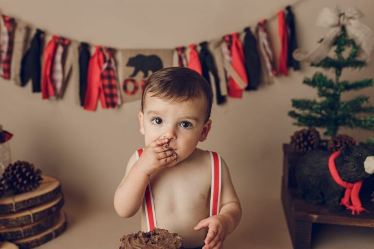 closeup of baby boy putting his first taste of cake into his mouth.  A fabric tassel banner is behind him with red and black fabric in buffalo plaid.