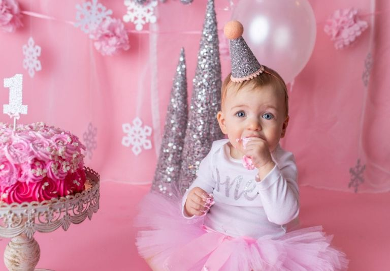 closeup of baby girl's face as she puts cake into her mouth during her cake smash photo session.