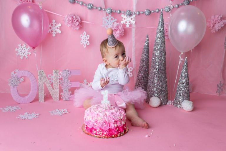 baby girl with a pink tutu skirt on eating pink cake with snowflake sprinkles on top for a wintery birthday theme.